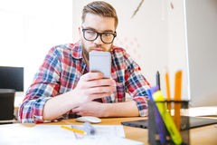 Handsome man sitting at the table and using cell phone Royalty Free Stock Images
