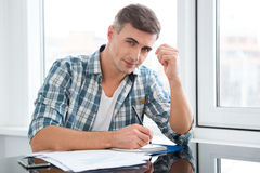 Handsome man sitting at the table and writing Royalty Free Stock Image
