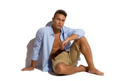 Handsome Man Is Sitting In Unbuttoned Shirt In Sunlight. Handsome young man in beige shorts and blue unbuttoned shirt is sitting relaxed against sunny wall and Royalty Free Stock Images