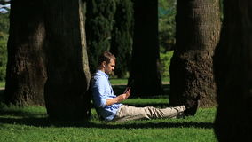 Handsome man sitting under a palm tree and browsing the Internet on a smartphone. Handsome man sitting under the tree and browsing internet on smartphone stock video footage