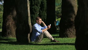 Handsome man sitting under a palm tree and browsing the Internet on a smartphone. Handsome man sitting under the tree and browsing internet on smartphone stock footage