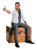 Handsome man sitting on a wooden chest and showing ok sign Royalty Free Stock Photos