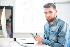 Handsome man sitting on workplace and using mobile phone Stock Image
