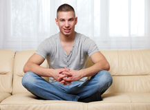 Handsome man sitting yoga-pose at home Stock Photos