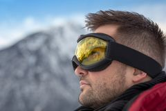 Handsome man with ski goggles looking up into the sky. In the mountains Stock Photos