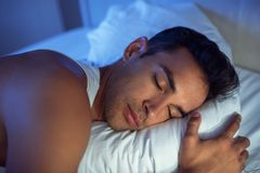 Beautiful close-up portrait of handsome man on the white bed. Handsome man sleep on the white bed Stock Photo