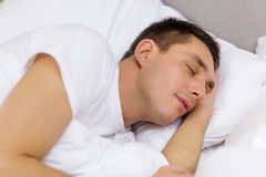 Handsome man sleeping in bed Stock Photos