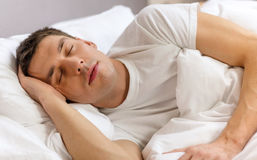 Handsome man sleeping in bed. Hotel, travel and happiness concept - handsome man sleeping in bed Royalty Free Stock Photo