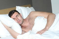 Handsome man sleeping in comfortable bed.  Royalty Free Stock Photos