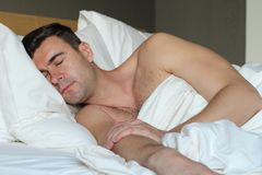 Handsome man sleeping in comfortable bed.  Royalty Free Stock Images