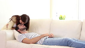 Handsome man sleeping on couch being woken by girlfriend stock video