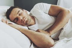 Handsome Man Sleeping in His Soft Bed at Some. Young Guy Wearing White Tshirt. People and Healthcare Concept. Side View. Healthcare Concept. Healthy Sleep stock photo