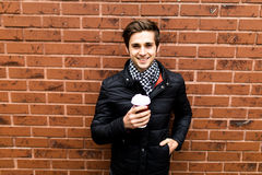 Handsome man in smart casual wear holding cup of coffee against brick wall. Handsome young man in smart casual wear holding cup of coffee against brick Royalty Free Stock Images