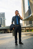 Handsome Man on smart phone - young business man in Modern City. Stock Photo