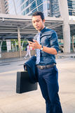 Handsome Man on smart phone - young business man in Modern City. Royalty Free Stock Images