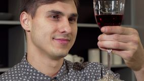 Handsome man smelling delicious red wine, relaxing at home. Cropped shot of a charming man smiling, enjoying smell of red wine. Happy man having glass of wine royalty free stock photos