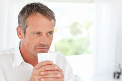 Handsome man smelling his coffee Stock Image
