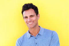 Handsome man smiling against yellow background Royalty Free Stock Photo
