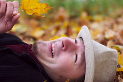 Handsome Man Smiling And Lying In Autumn Leaves Royalty Free Stock Images