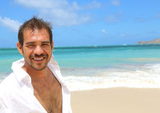 Handsome man smiling at beach Stock Image