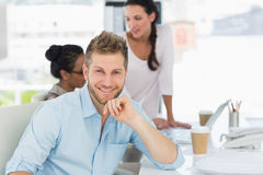 Handsome man smiling at camera while colleagues talk at desk Stock Images