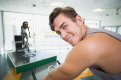 Handsome man smiling at camera in spin class Stock Photography
