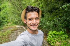 Handsome man smiling on the camera taking a selfie in a forest royalty free stock photography