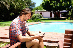 Handsome man smiling with cell phone next to pool Stock Photos