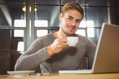 Handsome man smiling and drinking coffee Royalty Free Stock Images