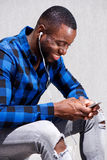 Handsome man smiling with earphones and mobile phone. Side portrait of handsome man smiling with earphones and mobile phone Royalty Free Stock Images