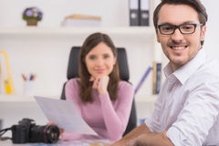 Handsome man is smiling on foreground. Stock Photo