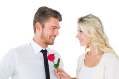 Handsome man smiling at girlfriend holding a rose Royalty Free Stock Images