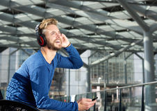 Handsome man smiling with headphones and mobile phone. Portrait of a handsome man smiling with headphones and mobile phone Stock Image