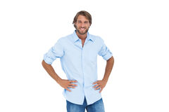 Handsome man smiling with his hands on hips Stock Images