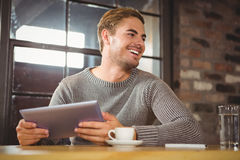 Handsome man smiling and holding tablet computer Stock Image