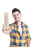Handsome man smiling and holding a wooden thermometer Royalty Free Stock Photos