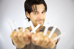 Handsome man smiling at many cigarettes Stock Photo