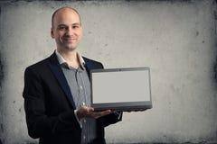 Handsome man smiling showing laptop Royalty Free Stock Photos