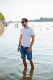 Handsome man smiling and standing in the water Royalty Free Stock Images