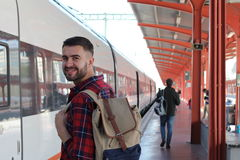 Handsome man smiling about to take train Royalty Free Stock Image