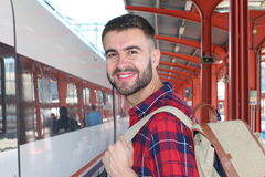 Handsome man smiling about to take a train Royalty Free Stock Photos