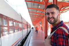 Handsome man smiling about to take a train with copy space Royalty Free Stock Photos
