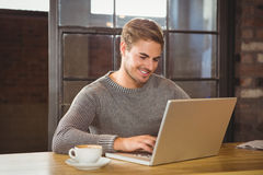 Handsome man smiling and typing on laptop Stock Photography