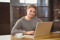Handsome man smiling and using laptop Stock Image