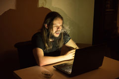 Handsome man is smocking cigarettes in front of his computer Royalty Free Stock Photo