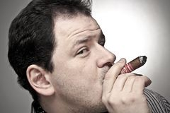 Handsome man smoking a cigar. Stock Images