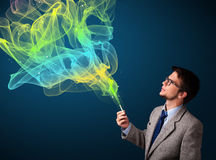 Handsome man smoking cigarette with colorful smoke Royalty Free Stock Photography