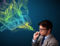 Handsome man smoking cigarette with colorful smoke stock images