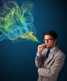 Handsome man smoking cigarette with colorful smoke Royalty Free Stock Photos