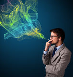 Handsome man smoking cigarette with colorful smoke Stock Image